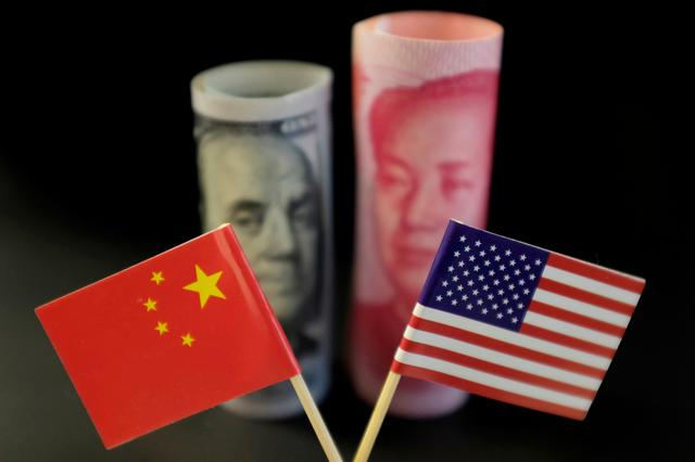 FILE PHOTO: U.S. and Chinese flags are seen in front of a U.S. dollar banknote featuring American founding father Benjamin Franklin and a China's yuan banknote featuring late Chinese chairman Mao Zedong in this illustration picture taken May 20, 2019. REUTERS/Jason Lee/Illustration/File Photo