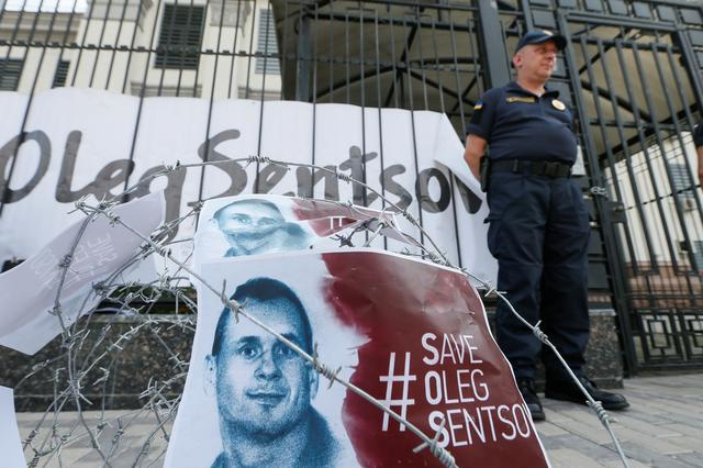 FILE PHOTO - Barbed wire and placards with images of Ukrainian film director Oleg Sentsov are seen after a rally demanding the release of Sentsov, who was jailed on terrorism charges and is currently on hunger strike in Russian jail, in front of the Russian embassy in Kiev, Ukraine August 21, 2018. REUTERS/Valentyn Ogirenko