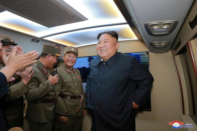 FILE PHOTO: North Korean leader Kim Jong Un smiles as he guides missile testing at an unidentified location in North Korea, in this undated image provided by KCNA on August 7, 2019.  KCNA via REUTERS