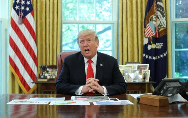 U.S. President Donald Trump talks to reporters as he receives a status report on Hurricane Dorian in the Oval Office of the White House in Washington, U.S., September 4, 2019. REUTERS/Jonathan Ernst