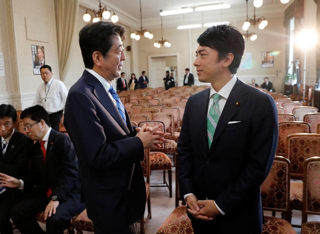 FILE PHOTO - Japan's Prime Minister Shinzo Abe (L) talks with his party's lawmaker Shinjiro Koizumi, son of former Prime Minister Junichiro Koizumi, at the party lawmakers' meeting after the dissolution of the lower house was announced at the Parliament in Tokyo, Japan September 28, 2017.  REUTERS/Kim Kyung-Hoon