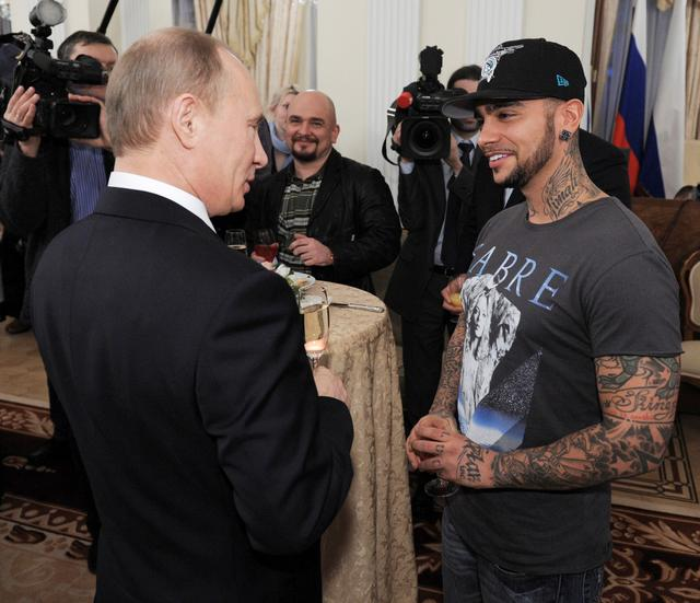 FILE PHOTO: Russian Prime Minister Vladimir Putin (L) talks to rapper Timati during a meeting with his supporters in Moscow March 5, 2012. REUTERS/Alexsey Druginyn/RIA Novosti/Pool