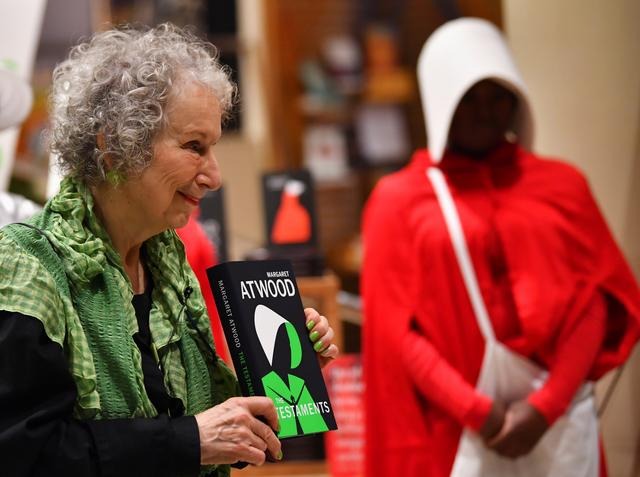 Author Margaret Atwood holds up her new novel The Testaments during the launch at a book store in London, Britain early September 10, 2019. REUTERS/Dylan Martinez