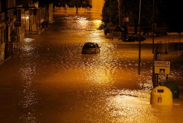 A car is stuck on a flooded street as torrential rains hit Orihuela, near Murcia, southeastern Spain, September 12, 2019. Picture taken September 12, 2019. REUTERS/Jon Nazca