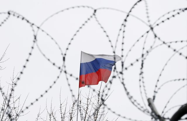 The Russian flag is seen through barbed wire as it flies on the roof of the Russian embassy in Kiev, Ukraine March 26, 2018. REUTERS/Gleb Garanich