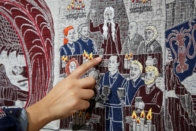 A visitor points at the Starbucks cup of the Game of Thrones Tapestry in Bayeux, France, September 13, 2019. REUTERS/Charles Platiau