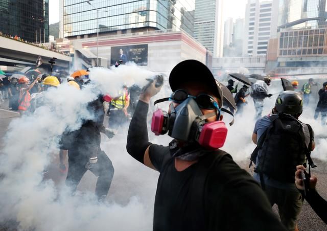 An anti-government protester throws back a tear gas canister at the police during a demonstration near Central Government Complex in Hong Kong, China, September 15, 2019. REUTERS/Jorge Silva