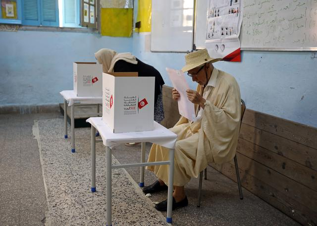 A man reads his ballot paper at a polling station during presidential election in Tunis, Tunisia, September 15, 2019. REUTERS/Muhammad Hamed