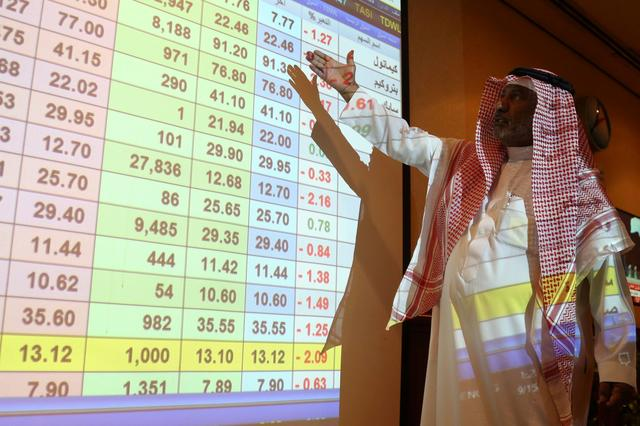 A saudi man inspect a screen showing stock prices at ANB Bank, in Riyadh Saudi Arabia September 15, 2019. REUTERS/Stringer