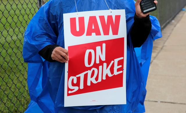 A member of United Auto Workers, Aramark workers, carries a strike sign outside the General Motors Detroit-Hamtramck assembly plant in Detroit, Michigan, U.S. September 15, 2019.   REUTERS/Rebecca Cook