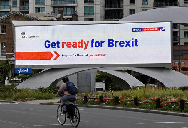 FILE PHOTO: A cyclist rides past an electronic billboard displaying a British government Brexit information awareness campaign advertisement in London, Britain, September 11, 2019. REUTERS/Toby Melville.