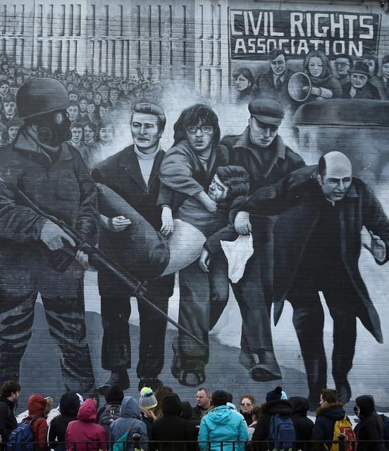 FILE PHOTO: Tourists stand in front of a mural depicting the Bloody Sunday events, in Londonderry, Northern Ireland March 14, 2019. REUTERS/Clodagh Kilcoyne/File Photo