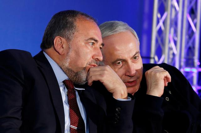 FILE PHOTO: Israel's Prime Minister Benjamin Netanyahu (R) converses with former Foreign Minister Avigdor Lieberman during a Likud-Yisrael Beitenu campaign rally in the southern Israeli city of Ashdod January 16, 2013. REUTERS/Amir Cohen/File Photo