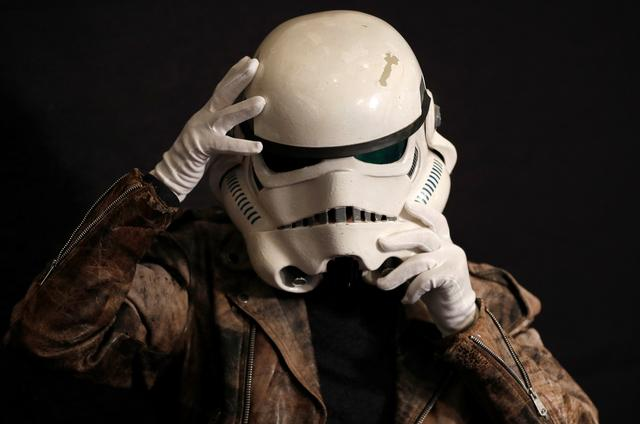 """Syd Wragg, who wore this Stormtrooper helmet in the film """"Star Wars: A New Hope"""", tries on the helmet again at a preview of a film and tv memorabilia sale in London, Britain, September 18, 2019.  REUTERS/Peter Nicholls"""