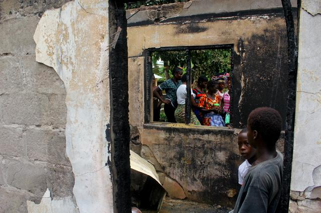 People walk through a burned building after a fire swept through a school killing children in Monrovia, Liberia September 18, 2019.    REUTERS/Stringer