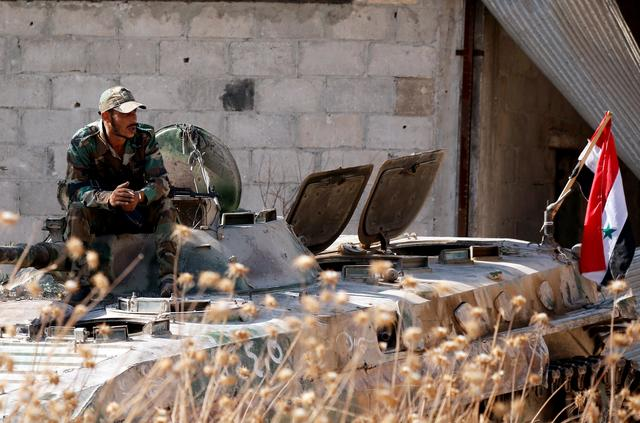 FILE PHOTO: A Syrian army soldier smokes cigarette as he sits on a military vehicle in Khan Sheikhoun, Idlib, Syria August 24, 2019. REUTERS/Omar Sanadiki/File Photo