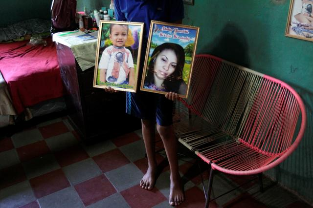 FILE PHOTO: Martin Hernandez, brother of late Honduran migrant Idalia Yamileth Herrera who drowned with her toddler Iker Gael Cordova while crossing the Rio Bravo to enter illegally into the U.S., holds framed pictures of his sister and nephew at her home in El Limon, Nacaome, Honduras September 19, 2019. REUTERS/Jorge Cabrera