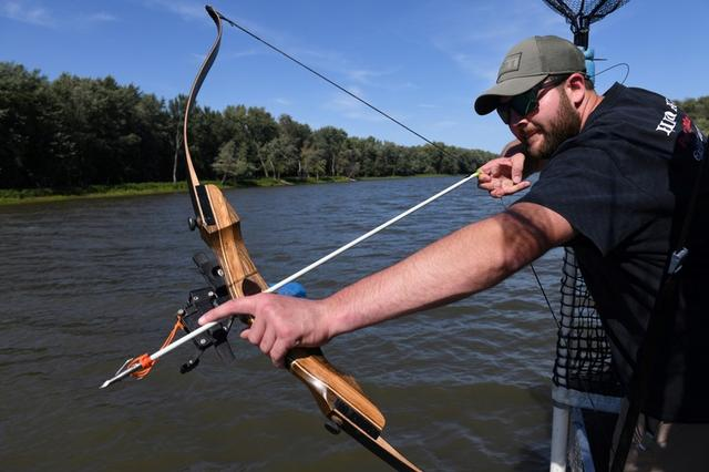 FILE PHOTO: Zach VandeVusse, 23, an electrician from Hamilton Michigan, lines up a shot on Captain Nate Wallick's boat while out hunting Asian carp with bow and arrow, on the Illinois River near Lacon, Illinois, U.S., September 14, 2019. REUTERS/Nicholas Pfosi