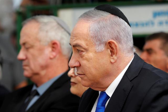 FILE PHOTO: Israeli Prime Minister Benjamin Netanyahu looks on as he sits next to Benny Gantz, leader of the Blue and White party, during a memorial ceremony for late Israeli President Shimon Peres, at Mount Herzl in Jerusalem September 19, 2019. REUTERS/Ronen Zvulun/File Photo