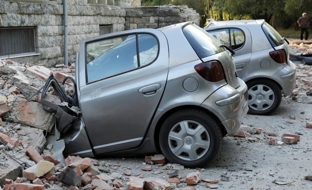 Destroyed cars stand next to a damaged building after an earthquake in Tirana, Albania, September 21, 2019. REUTERS/Florion Goga