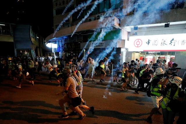 Protesters react to tear gas after a sit-in at Yuen Long to protest against violence that happened two months ago when white-shirted men wielding pipes and clubs wounded both anti-government protesters and passers-by, in Hong Kong, China September 21, 2019. REUTERS/Tyrone Siu