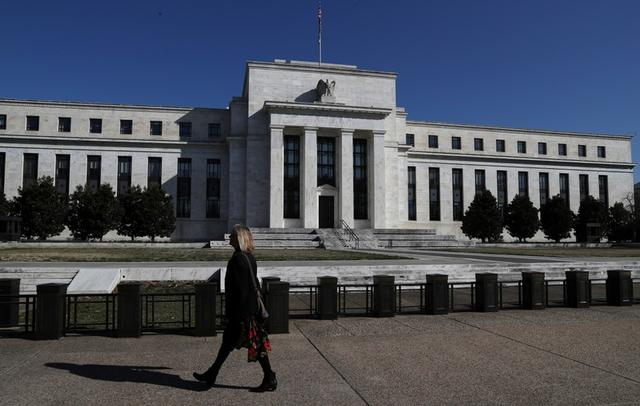 FILE PHOTO: A pedestrian walks past the Federal Reserve Board building on Constitution Avenue in Washington, U.S., March 19, 2019. REUTERS/Leah Millis