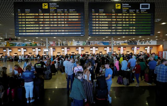 Thomas Cook passengers queue in front of check-in desks on the second day of repatriations at Reus airport, next to Tarragona, Spain, September 24, 2019. REUTERS/Albert Gea