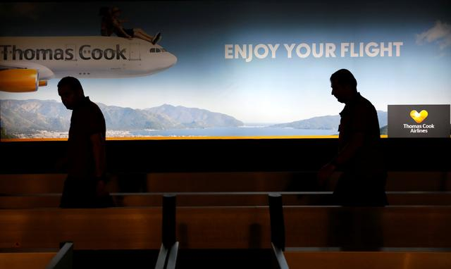 Men walk past a Thomas Cook banner at Dalaman Airport after Thomas Cook, the world's oldest travel firm, collapsed stranding hundreds of thousands of holidaymakers around the globe and sparking the largest peacetime repatriation effort in British history, in Dalaman, Turkey, September 23, 2019. REUTERS/Umit Bektas