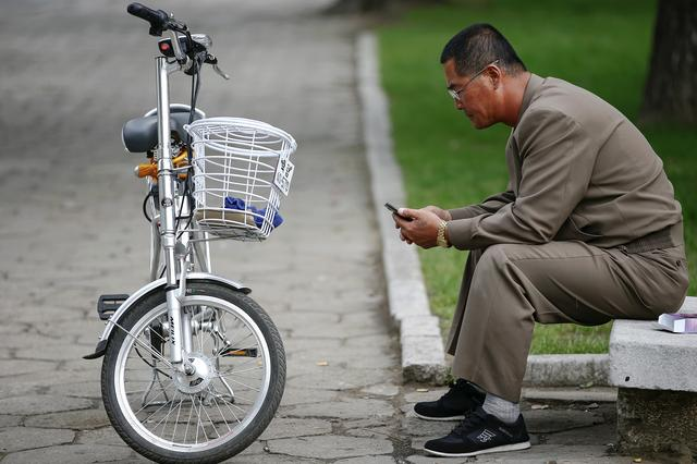 FILE PHOTO : A man uses his mobile phone next to an electric bicycle in downtown Pyongyang, North Korea October 8, 2015.   REUTERS/Damir Sagolj/File Picture