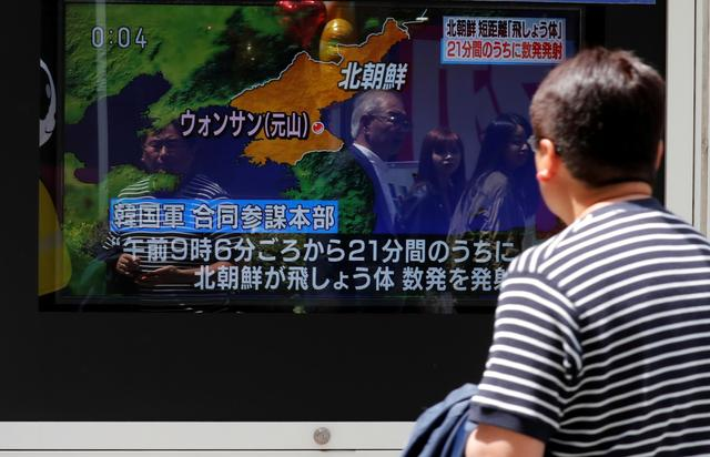 FILE PHOTO: A man watches a television screen showing a news report on North Korea firing several short-range projectiles from its east coast, on a street in Tokyo, Japan May 4, 2019. REUTERS/Kim Kyung-Hoon/File Photo