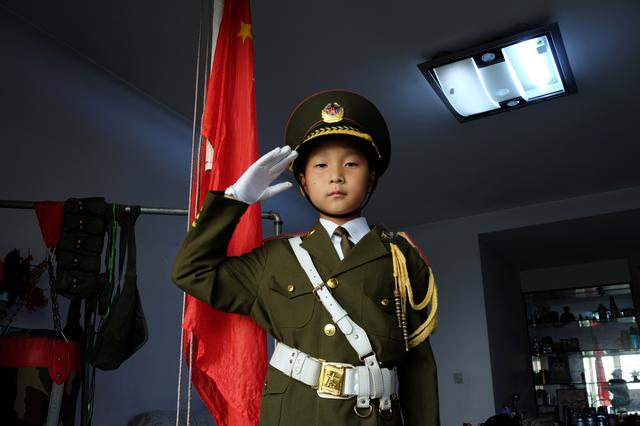 Feng Jianhan, 9, poses for a picture in military uniform next to a Chinese flag that he raises every morning through rope and pulley at his home in Xian, Shaanxi province, China September 26, 2019. REUTERS/Irene Wang