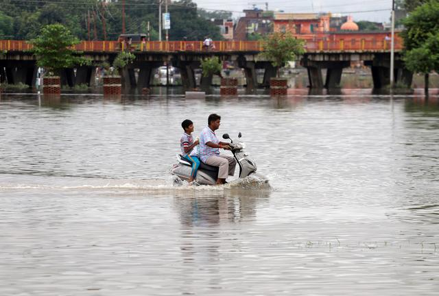 A man and a boy ride a scooter through a flooded road after heavy rains in Prayagraj, India, September 29, 2019. REUTERS/Jitendra Prakash