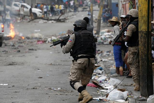 A Haitian National Police (PNH) officer walks across a street in Petion Ville to disperse demonstrators during a protest to demand the resignation of Haitian President Jovenel Moise in Port-au-Prince, Haiti, September 30, 2019. REUTERS/Andres Martinez Casares