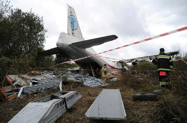 Members of emergency services work at the site of the Antonov-12 cargo airplane emergency landing in Lviv region, Ukraine October 4, 2019. REUTERS/Mykola Tys