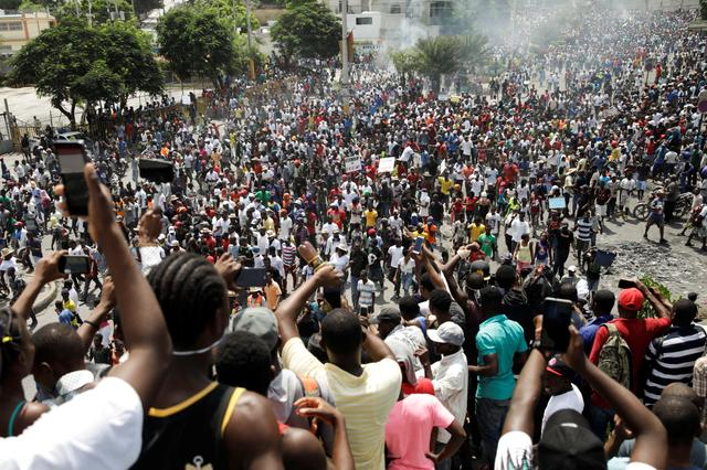 People take pictures with their cell phones as protesters march during a demonstration to demand the resignation of Haitian president Jovenel Moise, in the streets of Port-au-Prince, Haiti October 4, 2019. REUTERS/Andres Martinez Casares