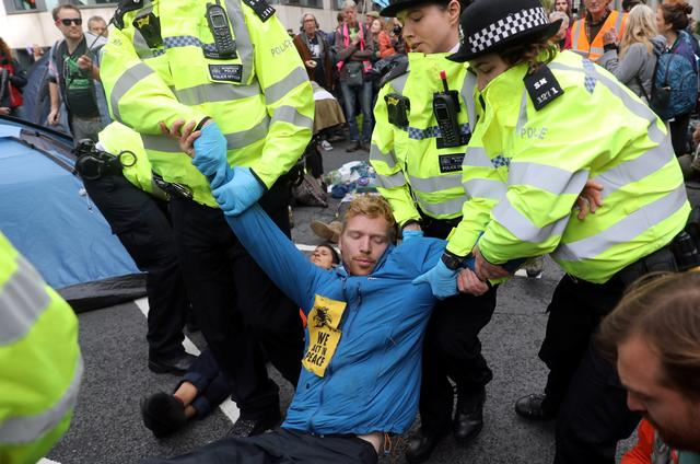 Police officers detain an Extinction Rebellion protester during a demonstration outside the Home Office in London, Britain, October 8, 2019. REUTERS/Simon Dawson