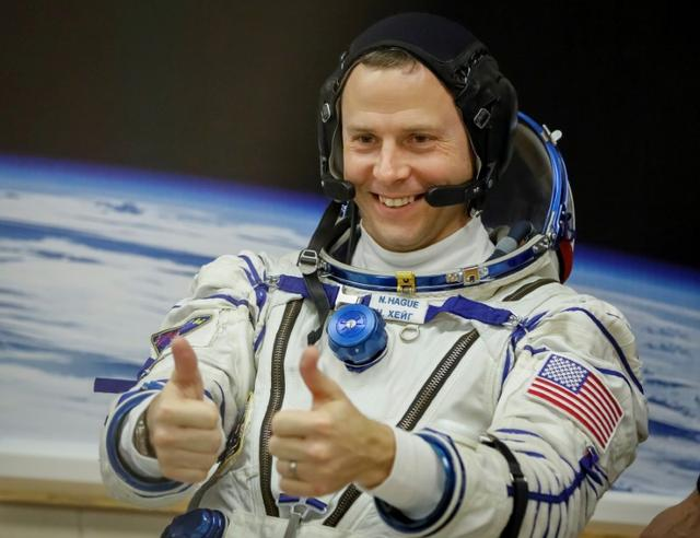 FILE PHOTO: The International Space Station (ISS) crew member Nick Hague of the U.S. gestures after donning space suits shortly before launch at the Baikonur Cosmodrome, Kazakhstan March 14, 2019.  REUTERS/Shamil Zhumatov/File Photo