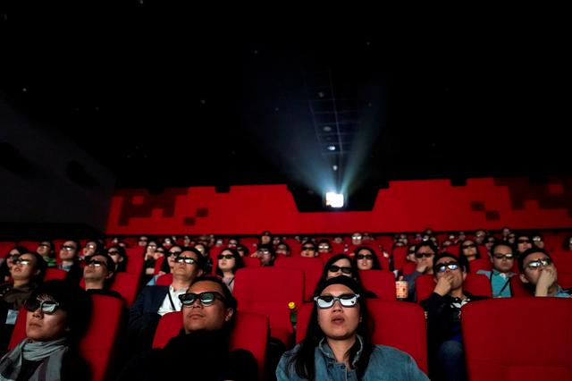 FILE PHOTO: People watch a movie at a cinema in Wanda Group's Oriental Movie Metropolis ahead of its opening, in Qingdao, Shandong province, China April 27, 2018. REUTERS/Aly Song