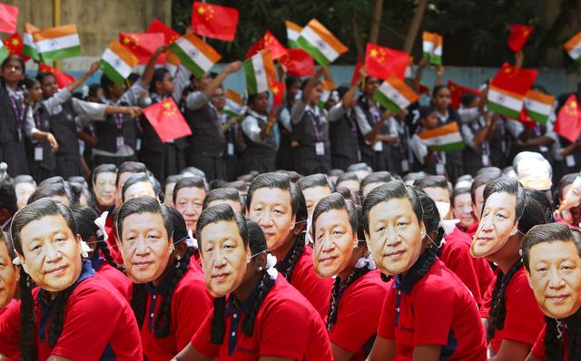Students wear masks of China's President Xi Jinping as other waves national flags of India and China, ahead of the informal summit with India's Prime Minister Narendra Modi, at a school in Chennai, India, October 10, 2019. REUTERS/P. Ravikumar