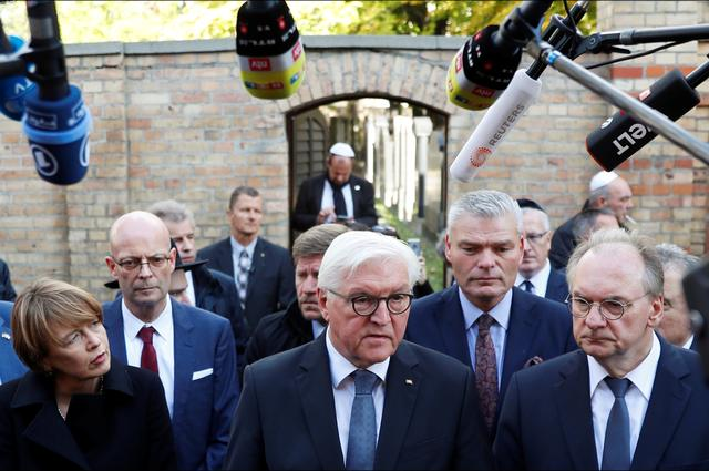 German President Frank-Walter Steinmeier speaks to the media next to his wife Elke Budenbender and Saxony-Anhalt State Premier Reiner Haseloff outside the synagogue in Halle, Germany October 10, 2019, after two people were killed in a shooting.  REUTERS/Fabrizio Bensch