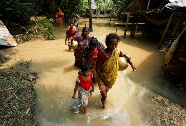 FILE PHOTO: People wade through a flooded road to collect drinking water in Howrah district, West Bengal, India August 2, 2017. REUTERS/Rupak De Chowdhuri