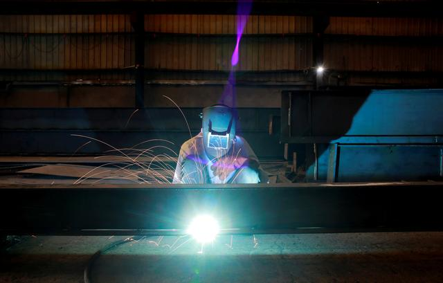 FILE PHOTO: A labourer welds an iron pillar at a building material factory in an industrial area in Dasna, Uttar Pradesh, India, January 9, 2019. REUTERS/Adnan Abidi/File Photo