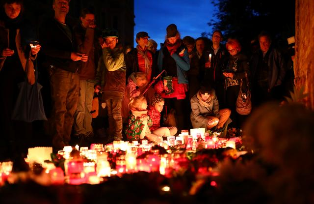 People gather around lit candles, placed outside the synagogue in Halle, Germany October 11, 2019, after two people were killed in a shooting. REUTERS/Hannibal Hanschke
