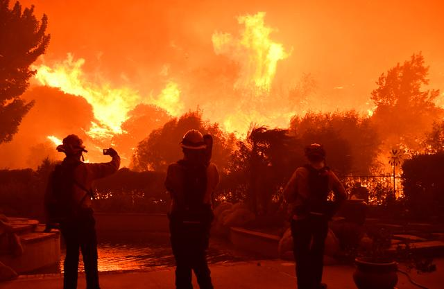 Firefighters battle a wind-driven wildfire called the Saddle Ridge fire in the early morning hours Friday in Porter Ranch, California, U.S., October 11, 2019.  REUTERS/ Gene Blevins