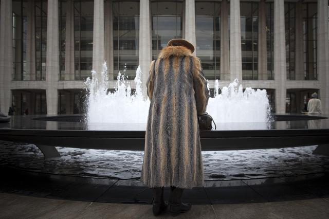 FILE PHOTO: A woman in a fur jacket goes through her handbag by the Lincoln Center's Revson Fountain during New York Fashion Week February 12, 2013. REUTERS/Andrew Kelly/File Photo