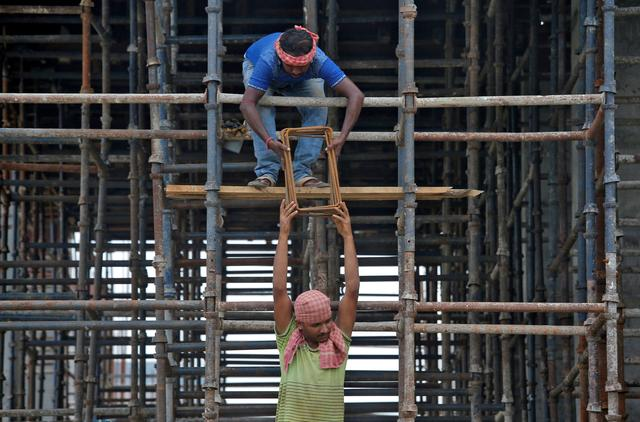 FILE PHOTO: Labourers work at the construction site of a residential building on the outskirts of Kolkata, India, July 5, 2019. REUTERS/Rupak De Chowdhuri/File Photo