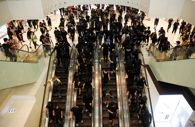 Anti-government protesters ride escalators during a demonstration at New Town Plaza shopping mall in Hong Kong, China, October 13, 2019. REUTERS/Umit Bektas