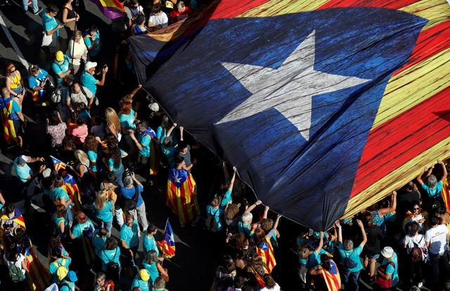 "FILE PHOTO: People hold a giant ""Estelada"" (Catalan separatist flag) at a rally during Catalonia's national day 'La Diada' in Barcelona, Spain, September 11, 2019. REUTERS/Albert Gea/File Photo"