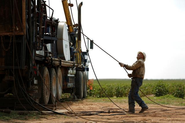 FILE PHOTO: Oil field worker, Miguel Holguin, operates a swabbing rig in a field in Seminole, TX, U.S. September 19, 2019.  REUTERS/Adria Malcolm