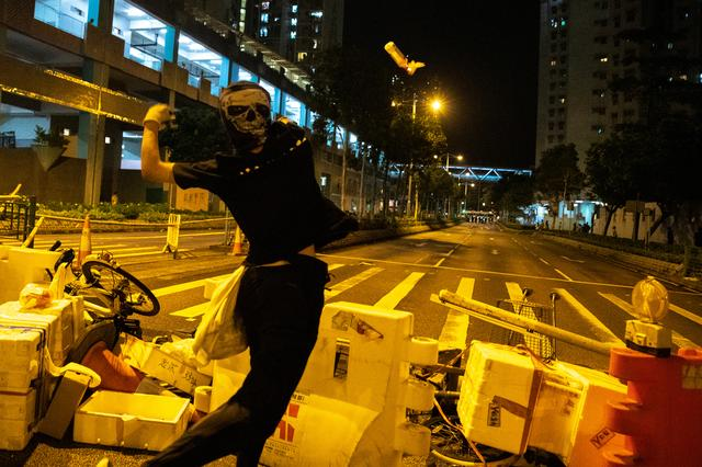 Anti-govenrment protesters throws a molotov cocktail toward riot police officers during a protest at Tseung Kwan O district, in Hong Kong, China, October 13, 2019. REUTERS/Athit Perawongmetha